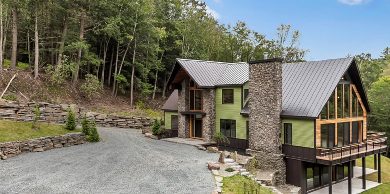 A photo of a green pocono cabin with stonewalls