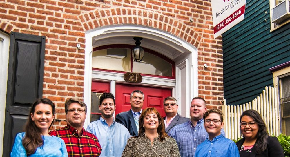 A photo of 9 Redstone Run Realty team members standing together in front of the office